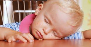 Small boy fell asleep on the table Stock Photography