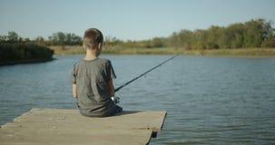 Small boy fisherman, catching a fish on a rod on the lake. Outdoors. Small boy fisherman, catching a fish on a rod on the lake. Outdoors stock footage