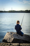 Small boy fishing from sea coast Royalty Free Stock Photos