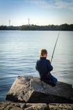 Small boy fishing from sea coast Royalty Free Stock Photos