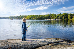 Small boy fishing in the sea Royalty Free Stock Image