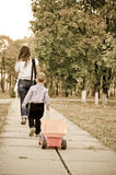 Small boy following Mum with a truck. Small boy following his mother down a rural paved pathway towing his toy truck along behind him Stock Photo