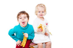 Small  boy and girl eating banans Royalty Free Stock Photography