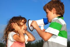 Small boy and girl play with loudspeaker. Small boy and the girl play with a loudspeaker, against the blue sky. Profile side Royalty Free Stock Images