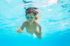 Small boy with goggles swims alone under water Stock Photos