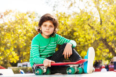 Small boy in green sweater holds red skateboard Royalty Free Stock Image
