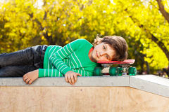 Small boy in green sweater laying on skateboard Royalty Free Stock Photo