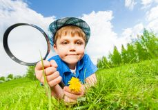 Small boy with hat holds magnifier laying on grass Royalty Free Stock Photo