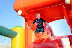 Small boy having fun on a jumping castle. Leaping in the air as he jumps down from the mouth of a plastic hippo Royalty Free Stock Photo