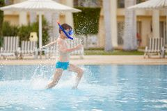 Small boy having fun with mask in swimming pool Royalty Free Stock Image