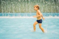 Small boy having fun runing in swimming pool royalty free stock image