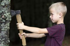 Small boy with heavy old iron axe cutting tree trump in forest on summer day. Outdoor activities and physical labor. Small boy with heavy old iron axe cutting stock image