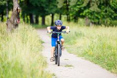 Small boy in helmet riding bicycle in park Royalty Free Stock Image