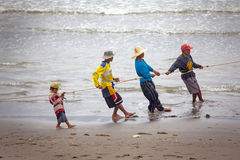 Small Boy Helping Adults Pulling Fish Net Royalty Free Stock Images