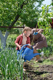 Small boy helping Mum water the vegetable garden. Standing with large blue plastic watering can while his mother works in background with hoe Stock Image