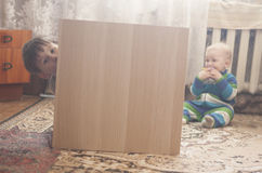 Small boy hiding behind wood furniture royalty free stock images