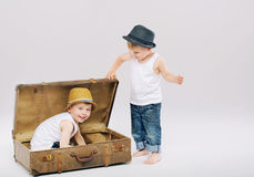 Small boy hiding his elder brother in suitcase Royalty Free Stock Photos