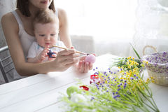 Small boy and his mother coloring Easter eggs at home. Royalty Free Stock Photography