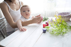 Small boy and his mother coloring Easter eggs at home. Royalty Free Stock Images