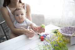 Small boy and his mother coloring Easter eggs at home. Royalty Free Stock Photo