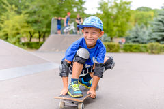 Small boy on his skateboard grinning at the camera Stock Photography