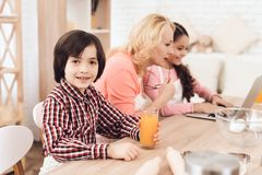 Small boy is holding glass of orange juice while sitting with his grandmother and sister in kitchen. stock images
