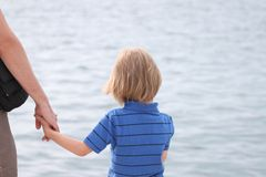 A small boy holds his father`s hand Royalty Free Stock Images