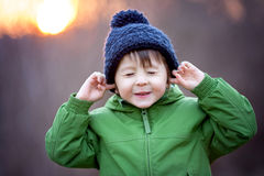 Small boy holds his hands over ears not to hear, making sweet fu Stock Images