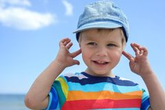 Small boy holds his hands over ears not to hear Royalty Free Stock Image