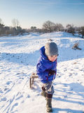 Small boy ipulling a sledge stock photos