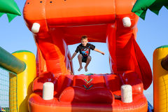 Small boy jumping in bouncy castle Stock Images