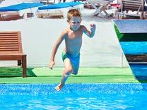 Small boy jumping into resort pool. Small boy jumping into a resort pool Royalty Free Stock Photos