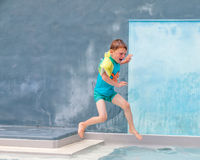 Small boy jumping into a swimming pool Royalty Free Stock Images