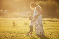 Small boy kissing belly of his pregnant mother. Outdoors Royalty Free Stock Photography