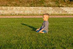 Small boy kneeling in green grass Stock Photos