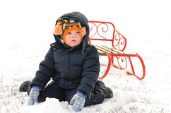 Small boy kneeling in the snow with a sled Stock Image