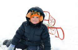 Small boy kneeling in the snow with a sled Royalty Free Stock Photos
