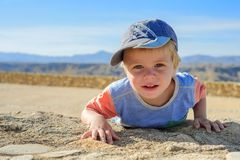 Small boy laying down on the rock Stock Photo