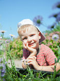 Small boy laying on the grass Stock Images