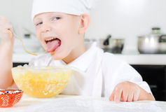 Small boy learning to cook checking his mixture Royalty Free Stock Photography