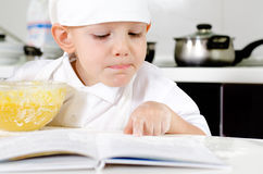 Small boy learning to cook checking his mixture Stock Image