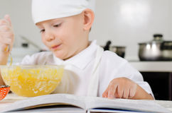 Small boy learning to cook checking his mixture Royalty Free Stock Image