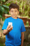 Small boy look into smartphone. Holding in front of him Royalty Free Stock Image