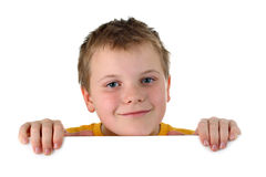 Small boy looking out of blank whiteboard smiling. Portrait of a preteen boy wearing yellow top, hidden behind a horizontal invisible empty banner, smiling a Stock Images