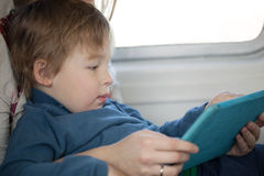 Small boy looking at a tablet in an airplane Stock Photos