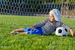 Small boy lying in the goalposts Stock Images