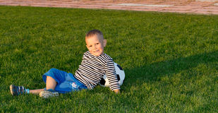 Small boy lying on green grass Stock Image