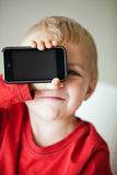 Small boy and media player. Small 3 year old toddler boy holding his media player with empty screen in his hand Royalty Free Stock Photos