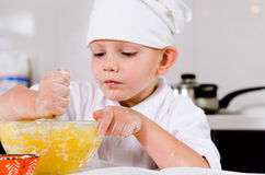 Small boy mixing ingredients for a cake in a bowl Royalty Free Stock Photos