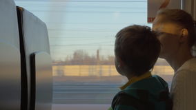 Small boy with mother sitting against window in their rail train place and watching outside on freight trains. Back view of small boy with mother sitting against stock video footage
